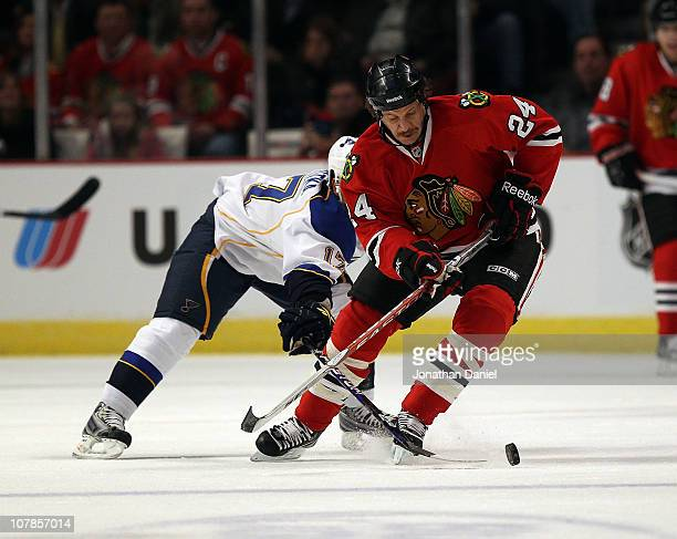 Nick Boynton of the Chicago Blackhawks tries to control the puck under pressure from Vladimir Sobotka of the St Louis Blues at the United Center on...
