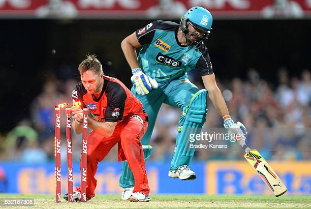 Nick Buchanan of the Heat is caught short of his ground by Nathan Rimmington of the Renegades during the Big Bash League match between the Brisbane...