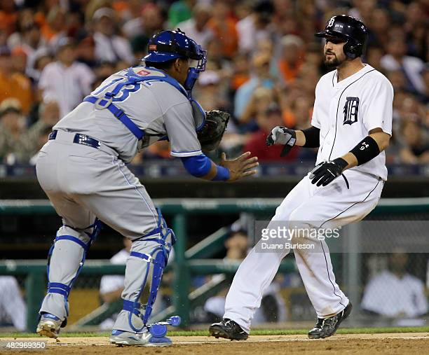 Nick Castellanos of the Detroit Tigers can't avoid the tag from catcher Salvador Perez of the Kansas City Royals for a double play during the seventh...
