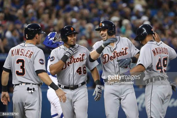 Nick Castellanos of the Detroit Tigers is congratulated by Ian Kinsler and Jeimer Candelario and Dixon Machado after hitting a grand slam home run in...
