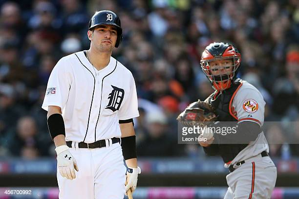 Nick Castellanos of the Detroit Tigers reacts as he strikes out to end the fourth inning as Nick Hundley of the Baltimore Orioles looks on during...
