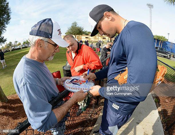 Nick Castellanos of the Detroit Tigers signs an autograph for a fan during the Tigers Workout Day at Joker Marchant Stadium on February 12 2014 in...