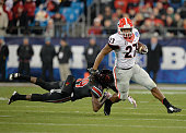 Nick Chubb of the Georgia Bulldogs breaks away from Terell Floyd of the Louisville Cardinals during the Belk Bowl at Bank of America Stadium on...