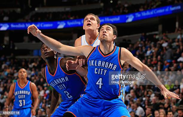 Nick Collison and Anthony Morrow of the Oklahoma City Thunder box out Timofey Mozgov of the Denver Nuggets at Pepsi Center on November 19 2014 in...
