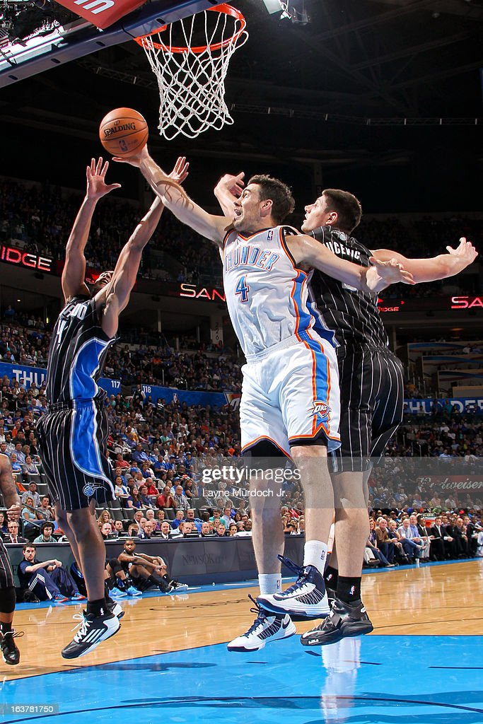 <a gi-track='captionPersonalityLinkClicked' href=/galleries/search?phrase=Nick+Collison&family=editorial&specificpeople=202843 ng-click='$event.stopPropagation()'>Nick Collison</a> #4 of the Oklahoma City Thunder reaches for a rebound against <a gi-track='captionPersonalityLinkClicked' href=/galleries/search?phrase=Arron+Afflalo&family=editorial&specificpeople=640861 ng-click='$event.stopPropagation()'>Arron Afflalo</a> #4 and Nikola Vucevic #9 of the Orlando Magic on March 15, 2013 at the Chesapeake Energy Arena in Oklahoma City, Oklahoma.