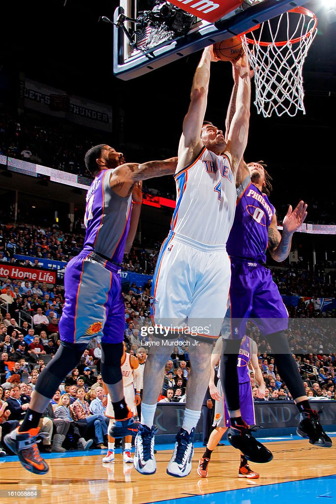 Nick Collison #4 of the Oklahoma City Thunder rises for a dunk against Markieff Morris #11 and Michael Beasley #0 of the Phoenix Suns on February 8, 2013 at the Chesapeake Energy Arena in Oklahoma City, Oklahoma.