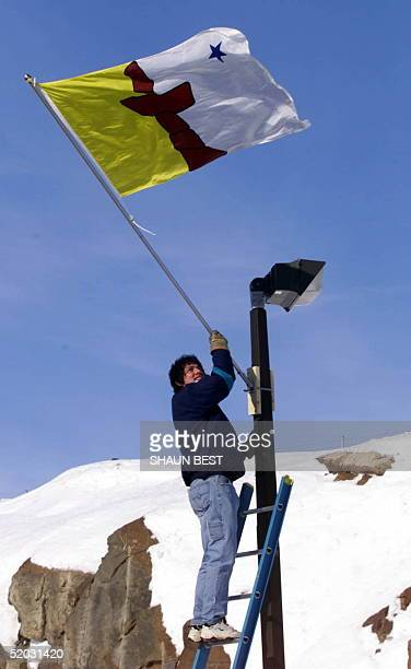Nick Cooper a public works employee is the first person to offically raise the new Nunavut flag in Iqaluit Canada 01 April 1999 A new territory...