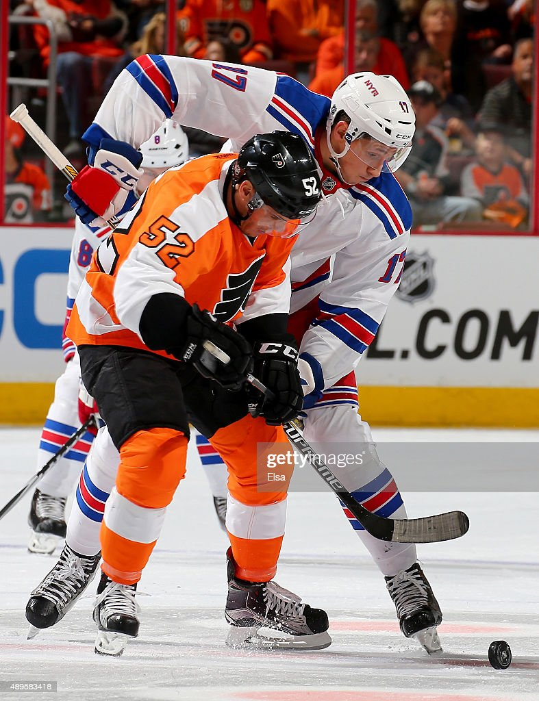 Nick Cousins of the Philadelphia Flyers and Luke Adam of the New York Rangers fight for the puck in the first period on April 7 2015 at the Wells...