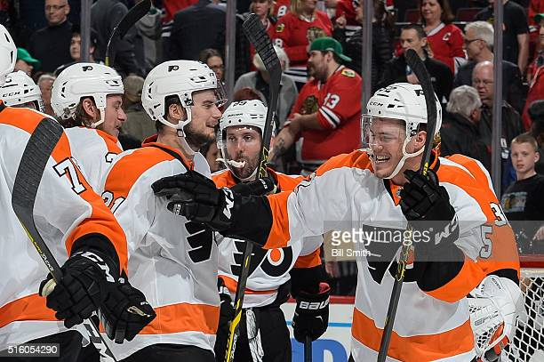 Nick Cousins of the Philadelphia Flyers celebrates with Scott Laughton after defeating the Chicago Blackhawks 3 to 2 during the NHL game at the...