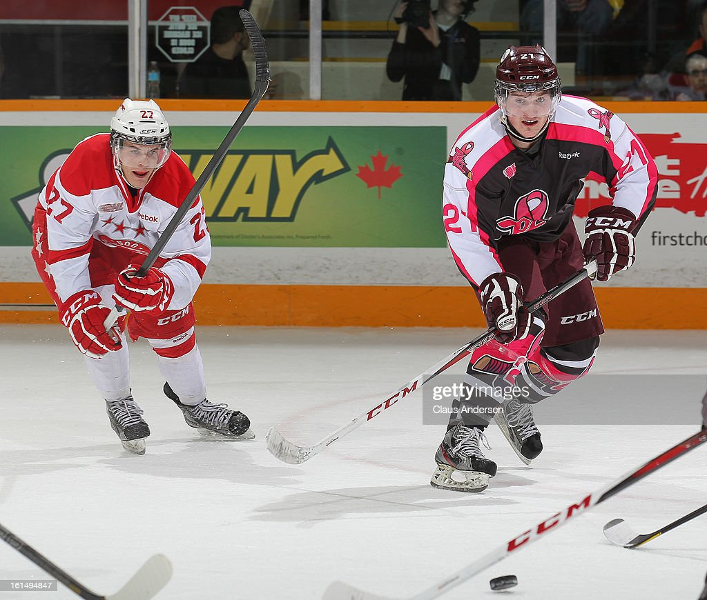 Nick Cousins #27 of the Sault Ste. Marie Greyhounds gets set to slash a puck away from Stephen Nosad #21 of the Peterborough Petes in an OHL game on February 9, 2013 at the Peterborough Memorial Centre in Peterborough, Ontario, Canada. The Petes defeated the Greyhounds 3-2.