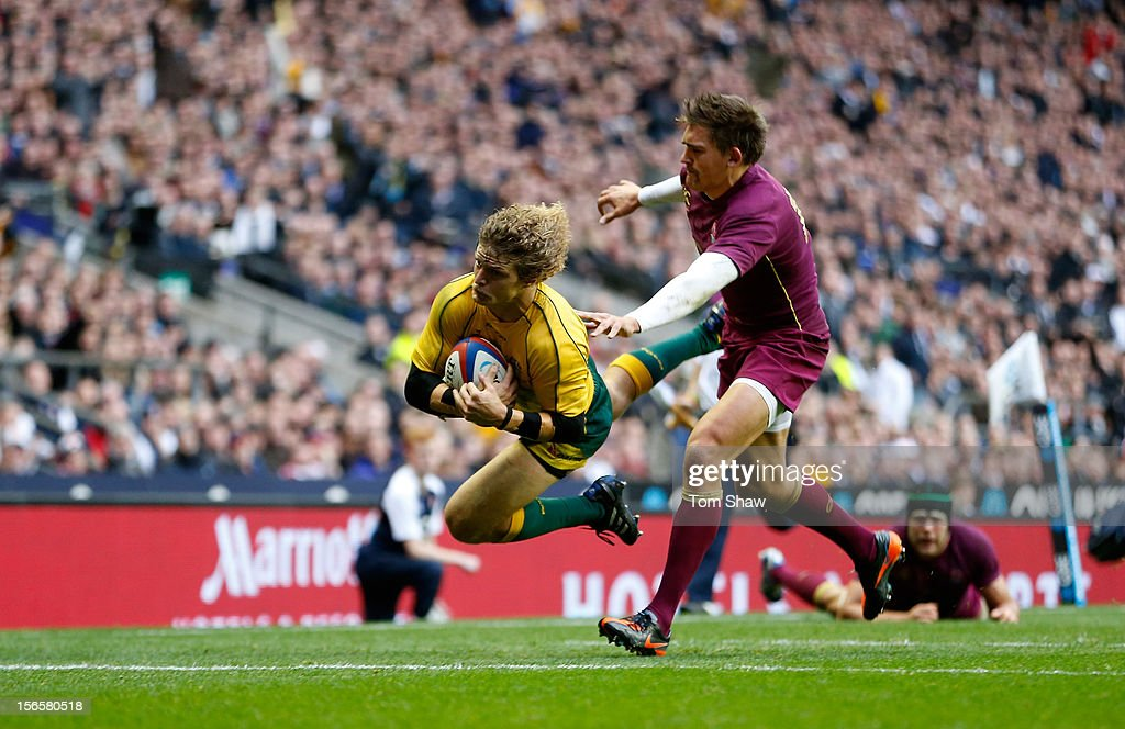 Nick Cummins (L) of Australia scores a try past <a gi-track='captionPersonalityLinkClicked' href=/galleries/search?phrase=Toby+Flood&family=editorial&specificpeople=551191 ng-click='$event.stopPropagation()'>Toby Flood</a> of England during the QBE International match between England and Australia at Twickenham Stadium on November 17, 2012 in London, England.