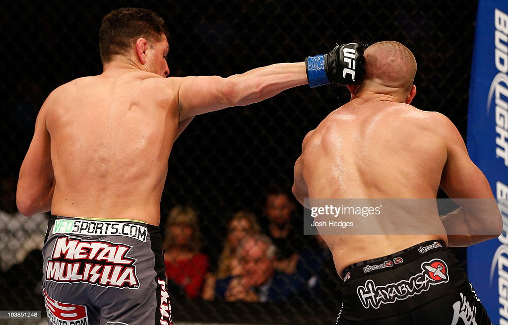 <a gi-track='captionPersonalityLinkClicked' href=/galleries/search?phrase=Nick+Diaz&family=editorial&specificpeople=5350175 ng-click='$event.stopPropagation()'>Nick Diaz</a> punches <a gi-track='captionPersonalityLinkClicked' href=/galleries/search?phrase=Georges+St-Pierre&family=editorial&specificpeople=4864241 ng-click='$event.stopPropagation()'>Georges St-Pierre</a> in their welterweight championship bout during the UFC 158 event at Bell Centre on March 16, 2013 in Montreal, Quebec, Canada.
