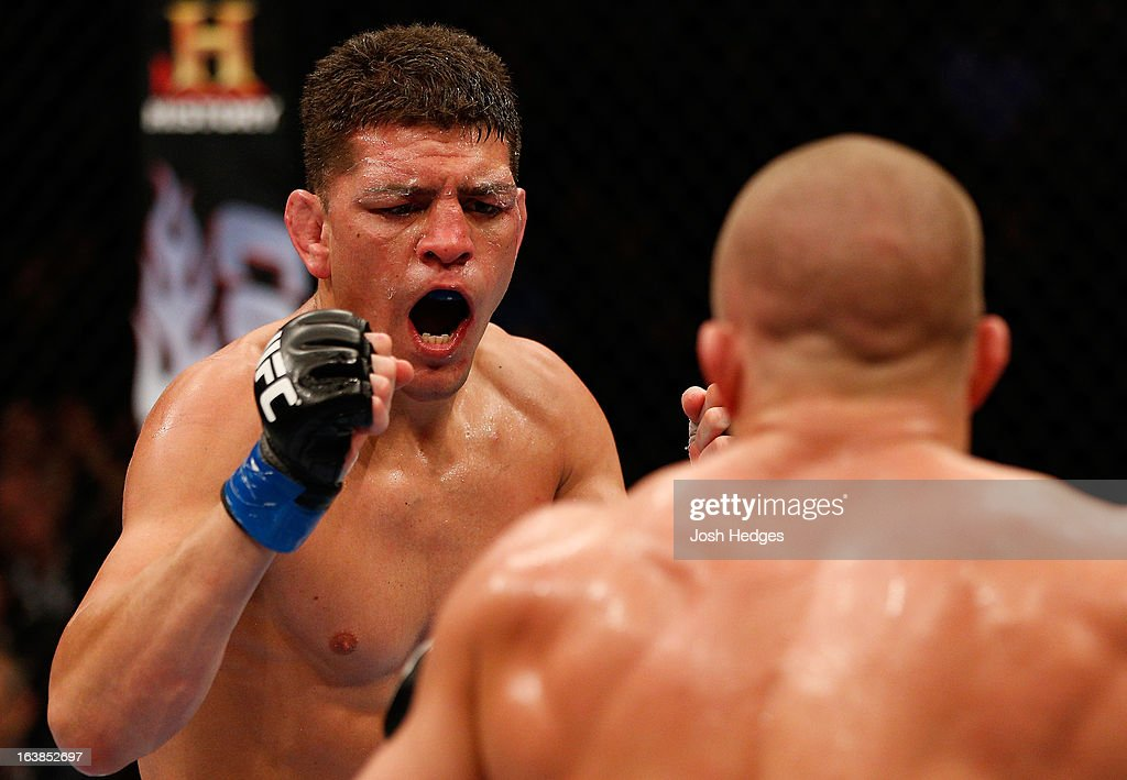 <a gi-track='captionPersonalityLinkClicked' href=/galleries/search?phrase=Nick+Diaz&family=editorial&specificpeople=5350175 ng-click='$event.stopPropagation()'>Nick Diaz</a> taunts <a gi-track='captionPersonalityLinkClicked' href=/galleries/search?phrase=Georges+St-Pierre&family=editorial&specificpeople=4864241 ng-click='$event.stopPropagation()'>Georges St-Pierre</a> in their welterweight championship bout during the UFC 158 event at Bell Centre on March 16, 2013 in Montreal, Quebec, Canada.