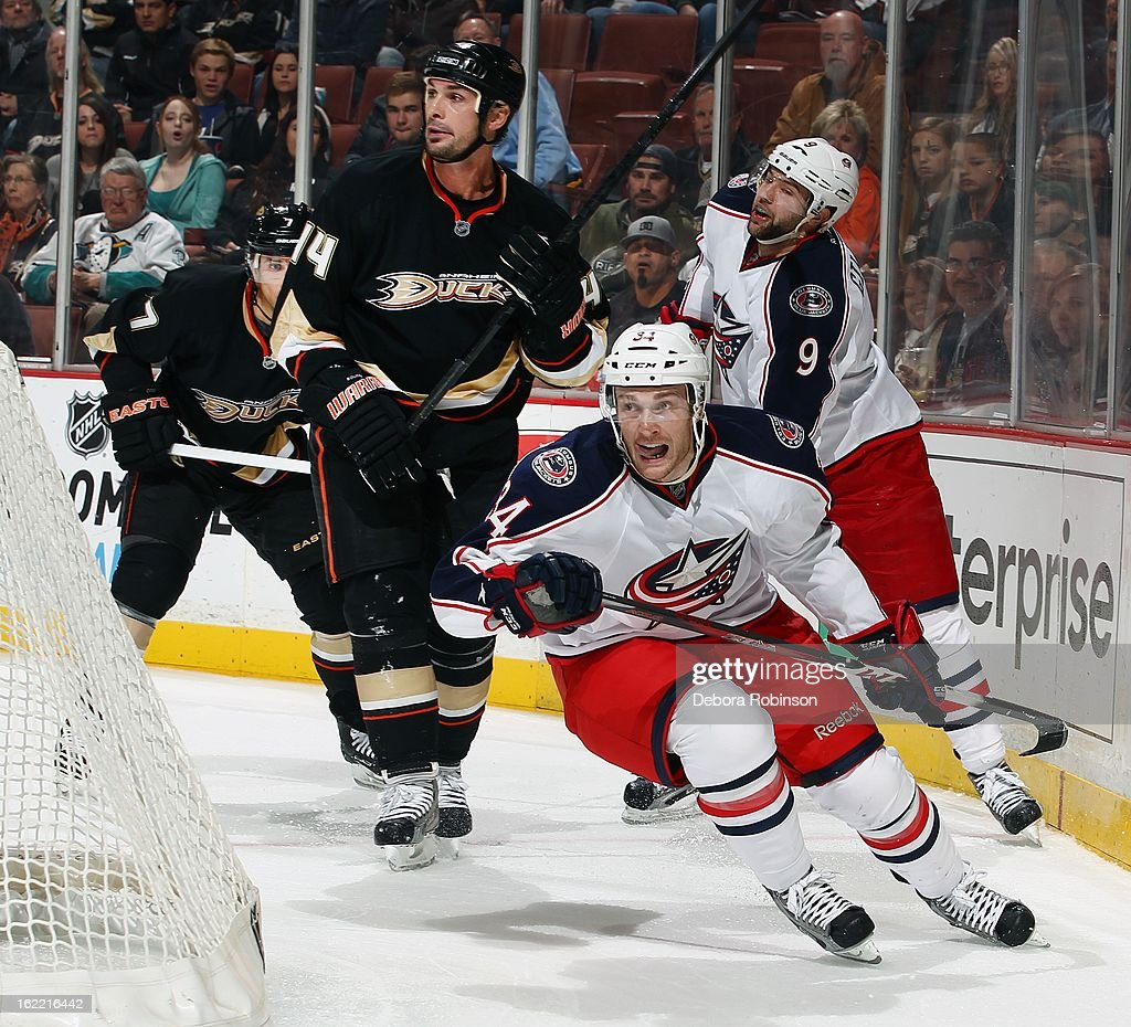 Nick Drazenovic #34 and Colton Gillies #9 of the Columbus Blue Jackets work to clear the puck from behind the net against Sheldon Souray #44 and Andrew Cogliano #7 of the Anaheim Ducks on February 18, 2013 at Honda Center in Anaheim, California.