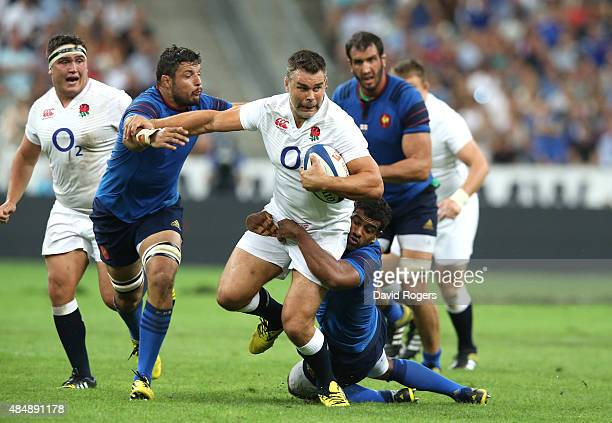 Nick Easter of England is tackled by Damien Chouley and Noa Nakaitaci during the International match between France and England at Stade de France on...