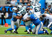 Nick Fairley and DeAndre Levy of the Detroit Lions tackle Jonathan Stewart of the Carolina Panthers at Bank of America Stadium on September 14 2014...