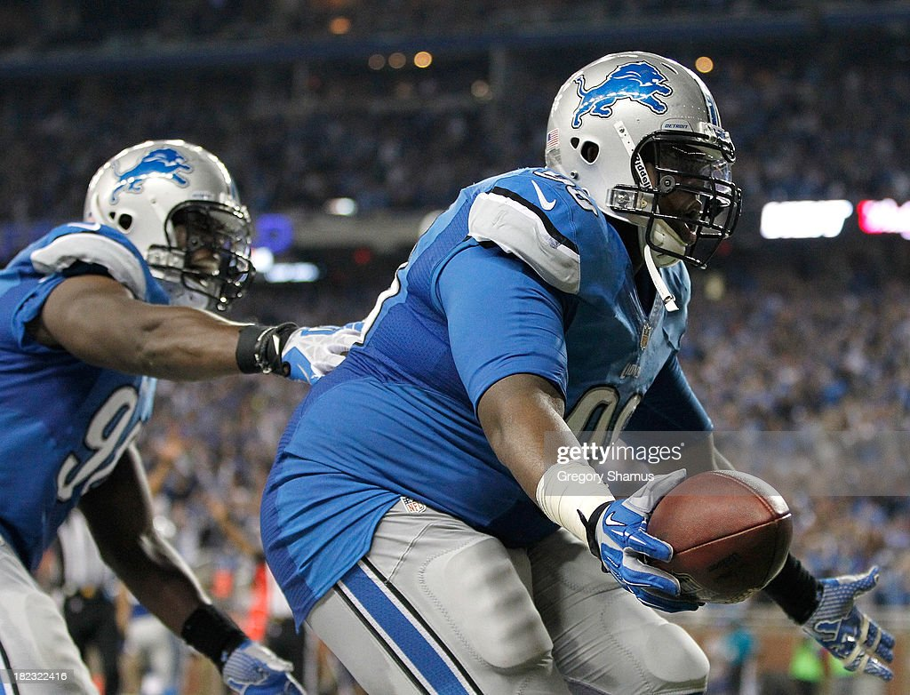 Nick Fairley #98 of the Detroit Lions celebrates a third quarter touchdown with Ezekiel Ansah #94 while playing the Chicago Bears at Ford Field on September 29, 2013 in Detroit, Michigan. Detroit won the game 40-32.