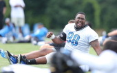 Nick Fairley of the Detroit Lions shares a laugh with fellow teammates during the third day of training camp on July 28 2013 in Allen Park Michigan
