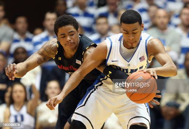 Nick Faust of the Maryland Terrapins and Quinn Cook of the Duke Blue Devils battle for a loose ball during their game at Cameron Indoor Stadium on...