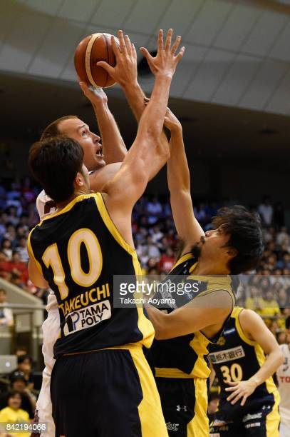Nick Fazekas of the Kawasaki Brave Thunders shoots while under pressure from Kosuke Takeuchi and Yuta Tabuse of the Tochigi Brex during the BLeague...