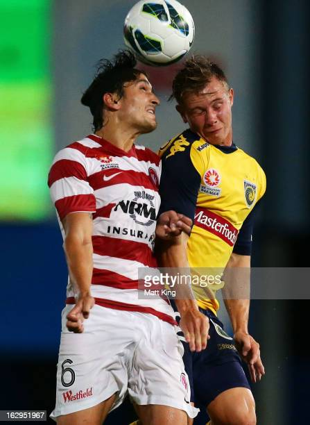 Nick Fitzgerald of the Mariners is challenged by Jerome Polenz of the Wanderers during the round 23 ALeague match between the Central Coast Mariners...
