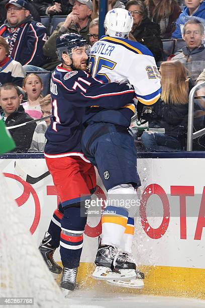Nick Foligno of the Columbus Blue Jackets checks Chris Butler of the St Louis Blues against the boards during the first period on February 6 2015 at...