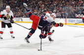 Nick Foligno of the Columbus Blue Jackets continues to play the puck after being hipchecked by Marc Methot of the Ottawa Senators during the third...
