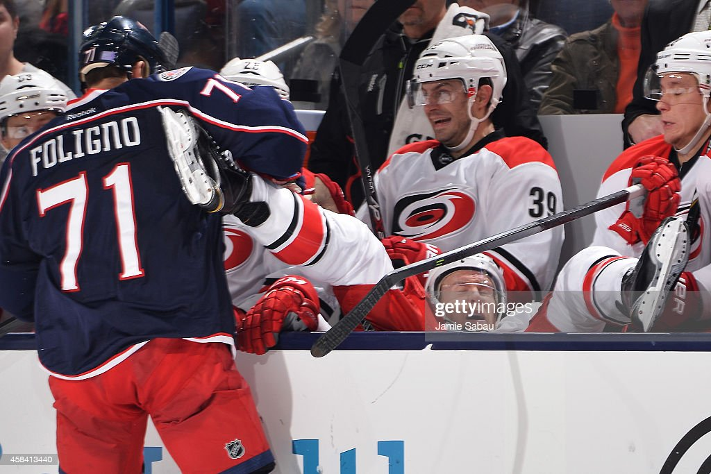 Nick Foligno of the Columbus Blue Jackets dumps Riley Nash of the Carolina Hurricanes back onto the bench with a check in the third period on...