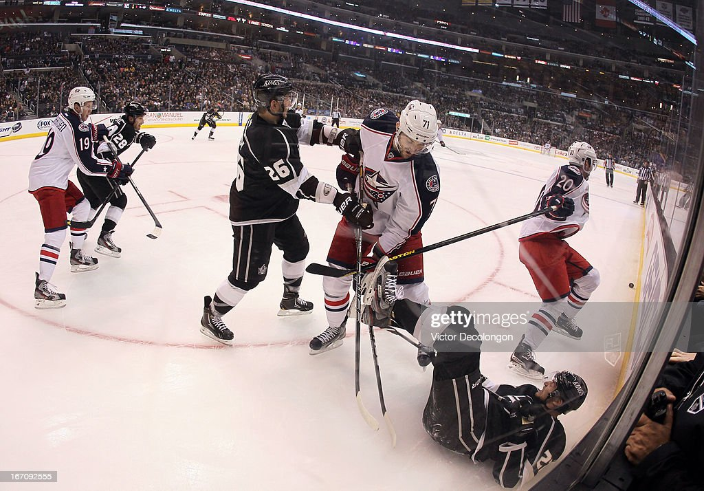 Nick Foligno #71 of the Columbus Blue Jackets gets his stick under the skates of Trevor Lewis #22 of the Los Angeles Kings as the play moves up ice in the third period during the NHL game at Staples Center on April 18, 2013 in Los Angeles, California. The Kings defeated the Blue Jackets 2-1.