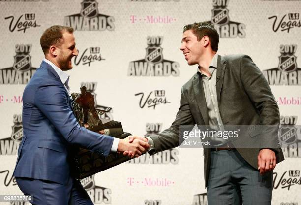 Nick Foligno of the Columbus Blue Jackets left and Travis Hamonic of the New York Islanders shake hands onstage during the 2017 NHL Humanitarian...