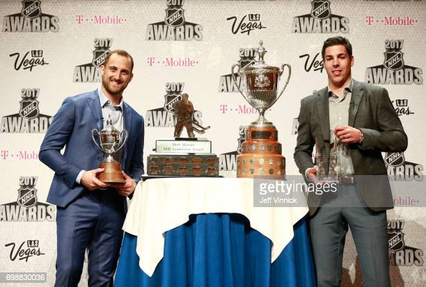 Nick Foligno of the Columbus Blue Jackets left poses with the King Clancy Memorial Trophy and the Mark Messer NHL Leadership Award for a photo...