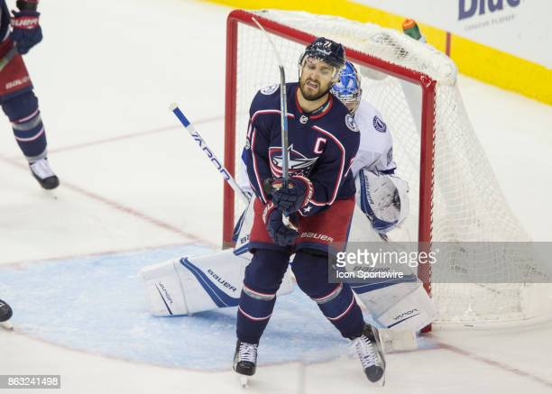 Nick Foligno of the Columbus Blue Jackets reacts to being hit with the puck in the third period of the game between the Columbus Blue Jackets and the...