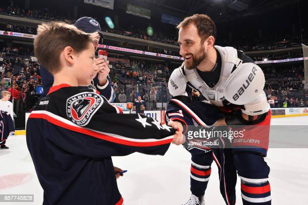 Nick Foligno of the Columbus Blue Jackets shakes hands with Archer Zimmerman before giving him his game jersey for jersey off our backs in honor of...