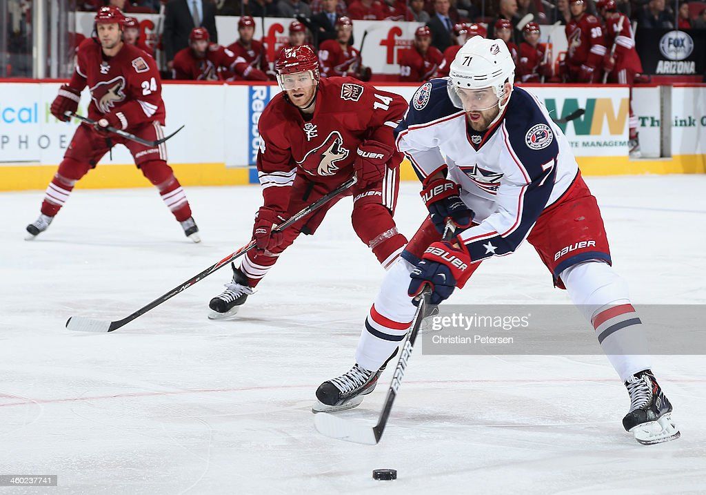 <a gi-track='captionPersonalityLinkClicked' href=/galleries/search?phrase=Nick+Foligno&family=editorial&specificpeople=537821 ng-click='$event.stopPropagation()'>Nick Foligno</a> #71 of the Columbus Blue Jackets skates in with the puck past <a gi-track='captionPersonalityLinkClicked' href=/galleries/search?phrase=Jeff+Halpern&family=editorial&specificpeople=206583 ng-click='$event.stopPropagation()'>Jeff Halpern</a> #14 of the Phoenix Coyotes during the third period of the NHL game at Jobing.com Arena on January 2, 2014 in Glendale, Arizona. The Blue Jackets defeated the Coyotes 2-0.