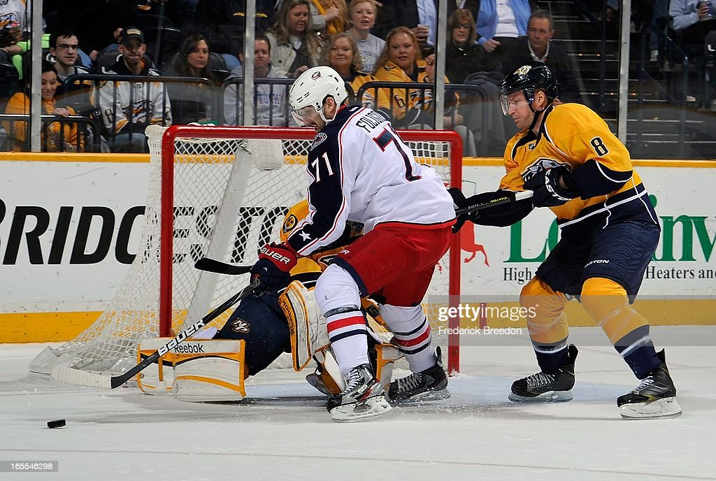 Nick Foligno #71 of the Columbus Blue Jackets tries to get a shot on goalie Pekka Rinne #35 of the Nashville Predators in front of Predators defenceman Kevin Klein #8 at the Bridgestone Arena on April 4, 2013 in Nashville, Tennessee.
