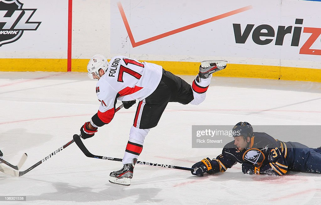 <a gi-track='captionPersonalityLinkClicked' href=/galleries/search?phrase=Nick+Foligno&family=editorial&specificpeople=537821 ng-click='$event.stopPropagation()'>Nick Foligno</a> #71 of the Ottawa Senators gets off a shot as Matt Ellis #37 of the Buffalo Sabres tries to defend at First Niagara Center on December 31, 2011 in Buffalo, New York. Ottawa won 3-2 in a shootout.