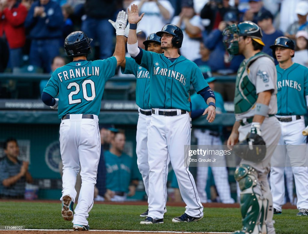 Nick Franklin #20 of the Seattle Mariners is congratulated by Brendan Ryan #26 after hitting a three-run home run against the Oakland Athletics in the third inning at Safeco Field on June 21, 2013 in Seattle, Washington.