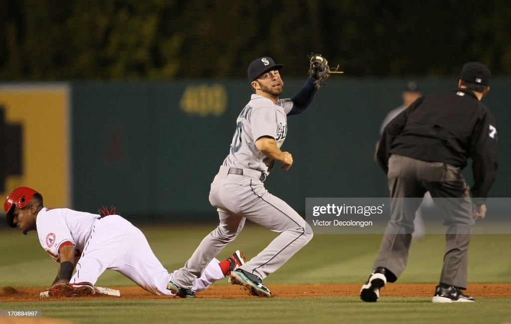 <a gi-track='captionPersonalityLinkClicked' href=/galleries/search?phrase=Nick+Franklin&family=editorial&specificpeople=3092191 ng-click='$event.stopPropagation()'>Nick Franklin</a> #20 of the Seattle Mariners looks to second base MLB umpire Jim Reynolds #77 for the call after tagging <a gi-track='captionPersonalityLinkClicked' href=/galleries/search?phrase=Erick+Aybar&family=editorial&specificpeople=551376 ng-click='$event.stopPropagation()'>Erick Aybar</a> #2 of the Los Angeles Angels of Anaheim on his steal attempt at second base in the fifth inning during the MLB game at Angel Stadium of Anaheim on June 19, 2013 in Anaheim, California. Aybar was safe at second base. It was Aybar's 100th career stolen base. The Angels defeated the Mariners 1-0.