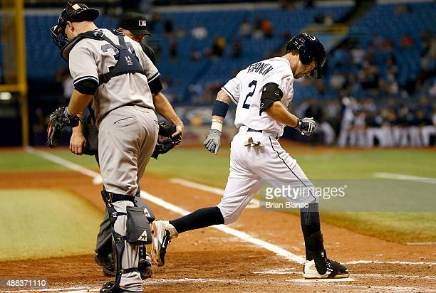 Nick Franklin of the Tampa Bay Rays crosses home plate in front of catcher Brian McCann of the New York Yankees after hitting a tworun home run...