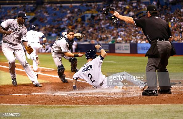 Nick Franklin of the Tampa Bay Rays slides safely into home plate ahead of catcher Francisco Cervelli of the New York Yankees and pitcher Michael...