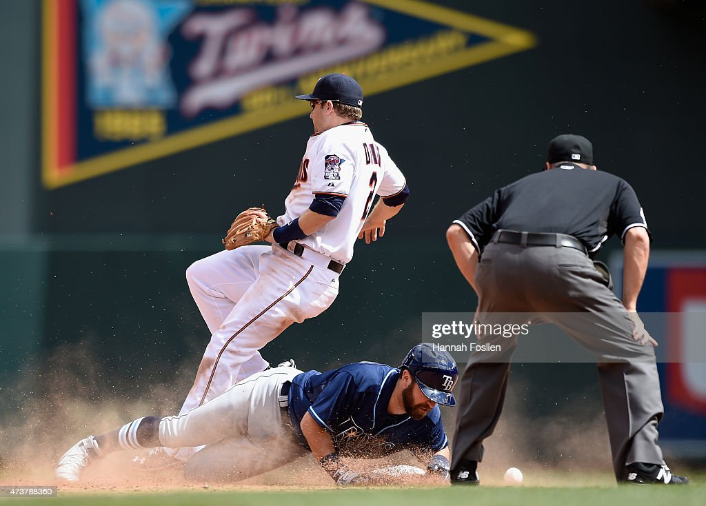 Nick Franklin of the Tampa Bay Rays slides safely into second with a double as Brian Dozier of the Minnesota Twins is unable to hold onto the ball...