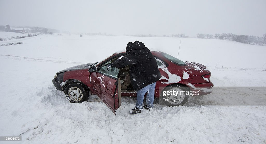 Nick Goetz leans against his car tired from pushing it out of the snow during a winter storm December 20, 2012 in Baraboo, Wisconsin. The State Patrol had warned motorists to stay home as a paralyzing winter storm bore down on Wisconsin, the first significant snowstorm to hit southern Wisconsin in two winters.