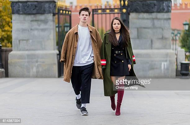 Nick Golubkov wearing a beige coat white oversized sweater and black pants and sneakers and Vika Kotova wearing a Balmain black blazer jacket green...