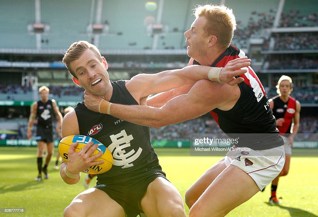 Nick Graham of the Blues is tackled by Adam Cooney of the Bombers during the 2016 AFL Round 06 match between the Carlton Blues and the Essendon Bombers at the Melbourne Cricket Ground, Melbourne on May 1, 2016.