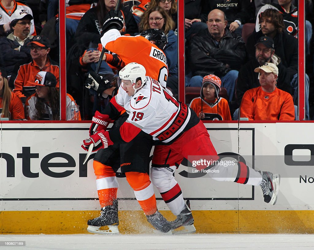 Nick Grossmann #8 of the Philadelphia Flyers is checked into the boards by Jiri Tlusty #19 of the Carolina Hurricanes on February 2, 2013 at the Wells Fargo Center in Philadelphia, Pennsylvania.