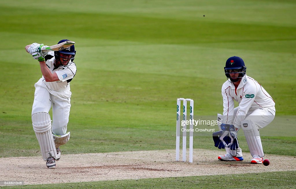 Nick Gubbins of Middlesex hits out while Steven Croft of Lancashire looks on duriung day two of the Specsavers County Championship division one match between Midlesex and Lancashire at Lords on June 27, 2016 in London, England.