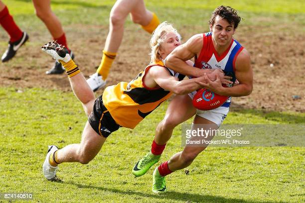 Nick Hogan of the Power is tackled by Mitch Cotter of the Stingrays during the round 14 TAC Cup match between Dandenong and Gippsland at Frankston...