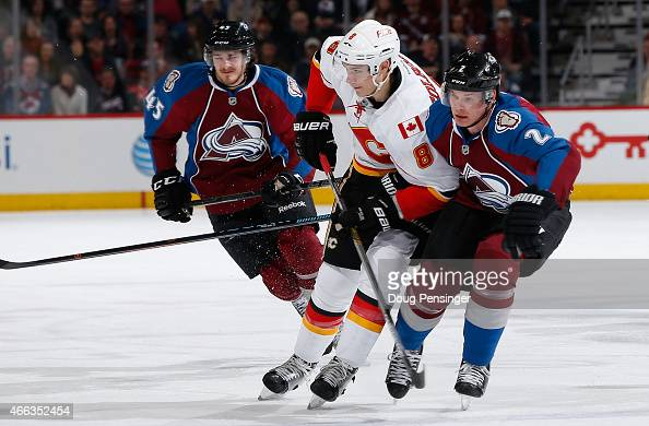 Nick Holden of the Colorado Avalanche defends against Joe Colborne of the Calgary Flames as Dennis Everberg of the Colorado Avalanche follows the...