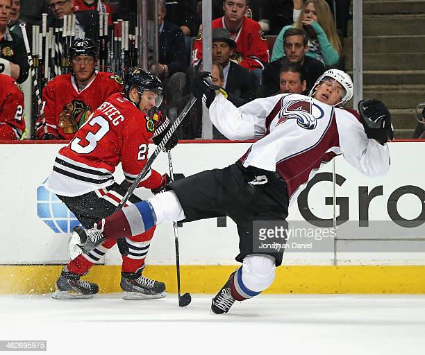 Nick Holden of the Colorado Avalanche falls to the ice trying to stop Kris Versteeg of the Chicago Blackhawks at the United Center on January 14 2014...
