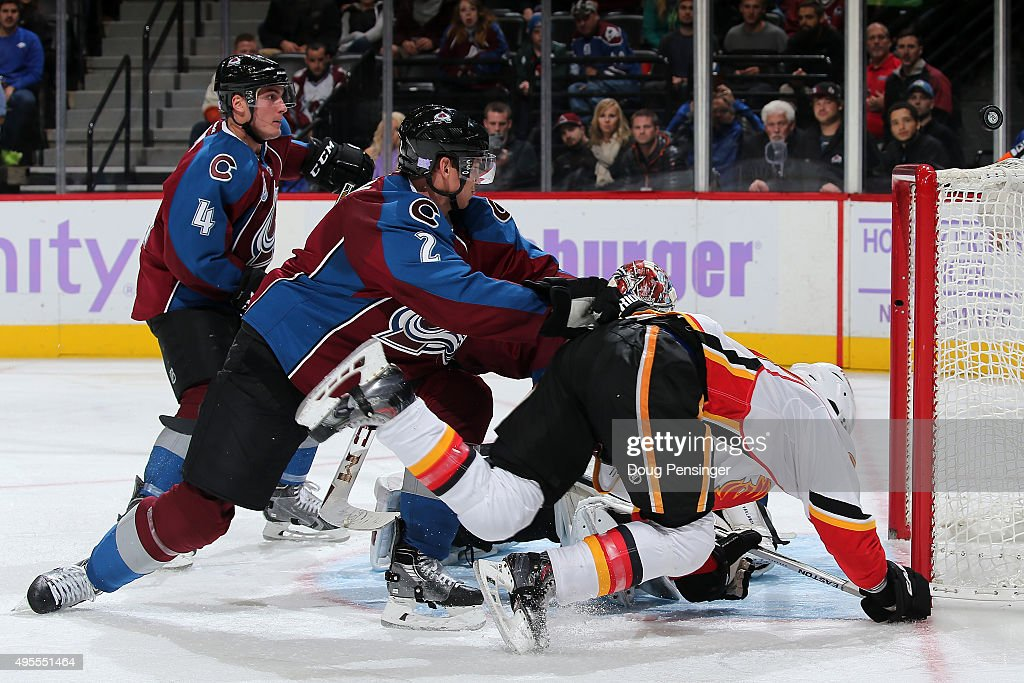Nick Holden #2 of the Colorado Avalanche puts a hit on Sam Bennett #93 of the Calgary Flames as the puck flies over the goal at Pepsi Center on November 3, 2015 in Denver, Colorado. The Avalanche defeated the Flames 6-3.